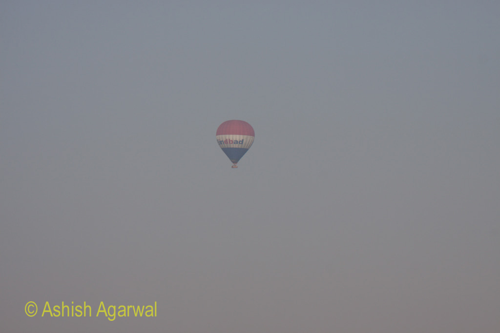 A hot air balloon flying over the Luxor countryside
