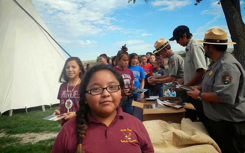 DOI/VISTA Josh Little Owl and NPS employees of Bighorn Canyon pass out booklets to Pretty Eagle Catholic Academy Students at Little Bighorn Battlefield.