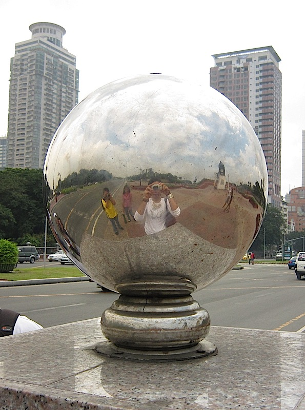 my reflection on the silver ball of the Kilometer 0 marker