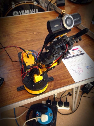 A Raspberry Pi Controlled Robot Arm with a laser pointer and webcam mounted on the end.  Created by Emsity.