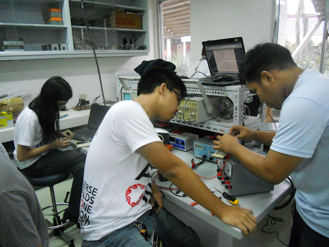 Mr. Lyndon Olaguera (right) teaches a student how to use the power supply