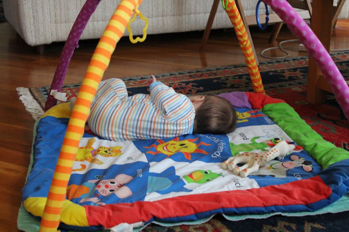 on her side on the play mat