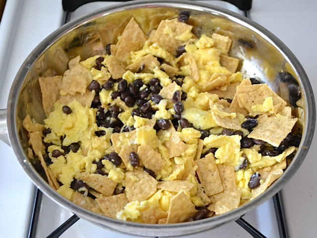tortilla chips, beans and eggs folded together in skillet