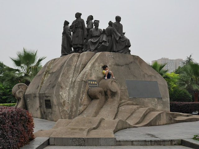 small girl eating ice cream while sitting below statues of Chinese scholars in traditional clothing