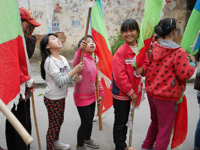 girls holding flags during the Nian Li Festival (年例节) in Maoming, China