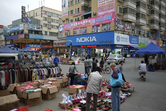 People selling clothes and shoes on the street and store with a large Nokia sign in the background