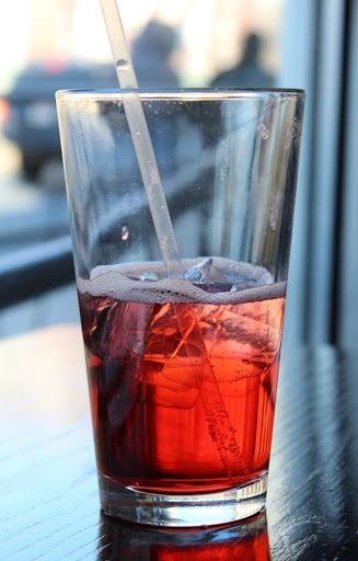 half-finished glass of cranberry and soda with ice