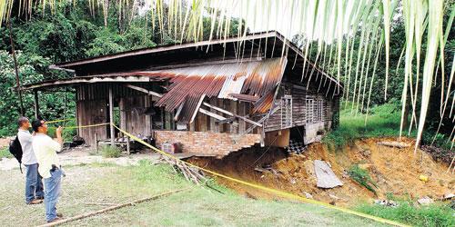 Penduduk kampung melihat keadaan rumah Wan Mah Wan Ali yang runtuh dalam kejadian yang berlaku di Kampung Sungai Charu, Jalan Sungai Lembing, Kuantan, semalam.