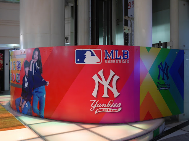 advertisement in Shanghai for MLB clothing with the New York Yankees logo above a logo for the Staten Island Yankees