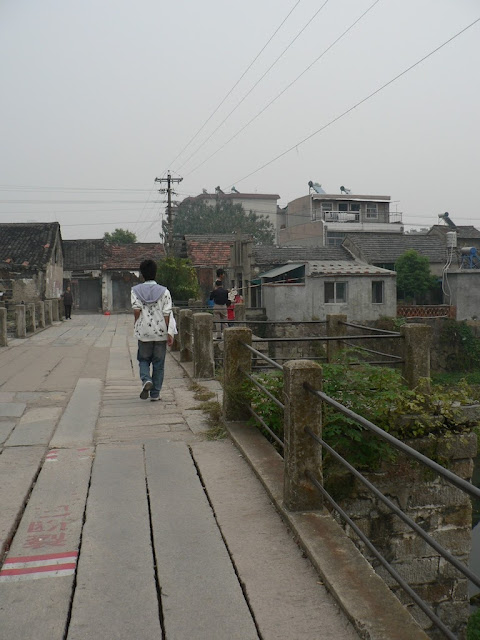 person walking on an old bridge in Tongcheng, Anhui, China
