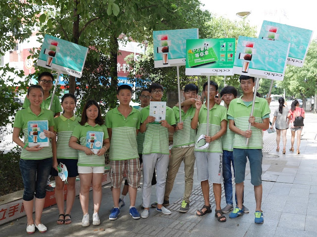 group of people wearing Oppo shirts and hold Oppo signs and other promotional material