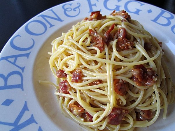 side view of spaghetti with bacon on a white plate with blue writing around the edges