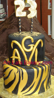 Two tier black and gold fondant custom designed Aries and zebra 23rd birthday cake