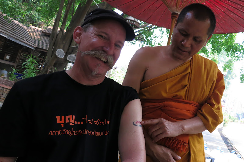 Phra Khru Phithak inspects Kevin's Carabao tattoo