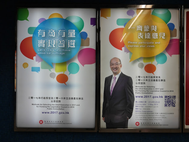 "signs in Hong Kong saying ""Let's talk and achieve universal suffrage"" and ""Please participate and express your views"""