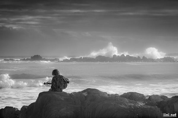 ảnh chàng trai buồn với cây đàn guitar hát trước biển