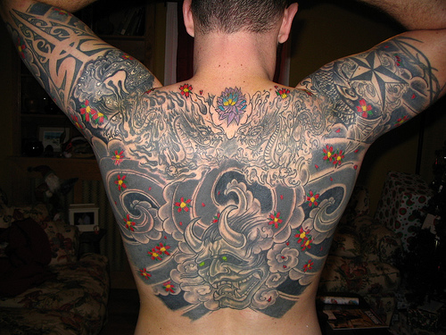 71324570e Here man with japanese tattoos design on his shoulders.Japanese oni mask  tattoo with koi dragon and foo dog covering man's upper back and shoulders.