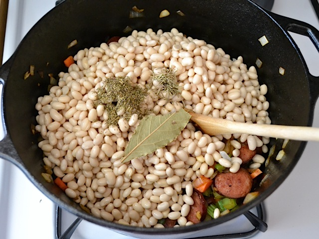 soaked beans and herbs added to the soup pot