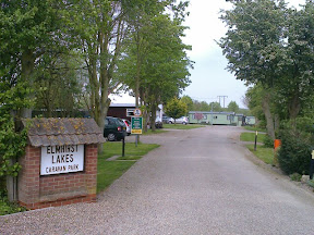 scenic gravelled chalet park entrance with large caravans in distance under trees
