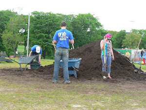 volunteers and a large pile of soil