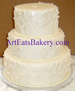Three tier white fondant unique custom wedding cake with pearl branches and leaves design
