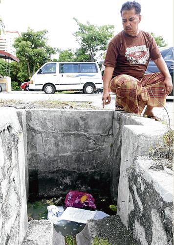 DI SINI...Mohammad menunjukkan longkang tempat dia ditinggalkan selepas dibelasah