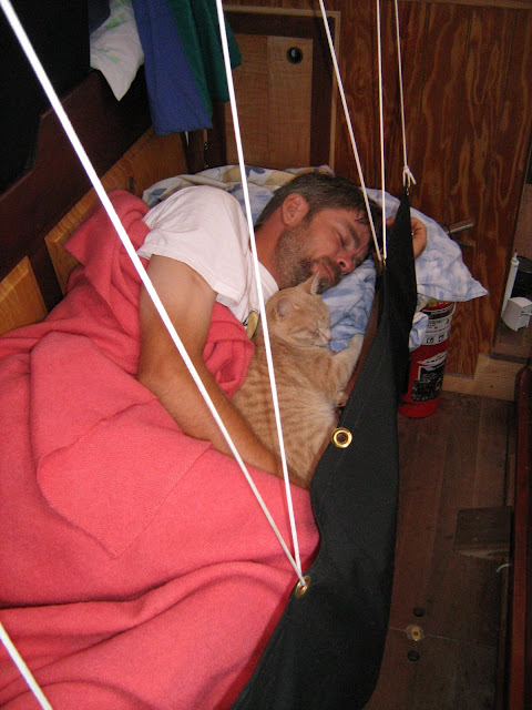 Mike and Oliver napping on a settee after a long night of sailing.