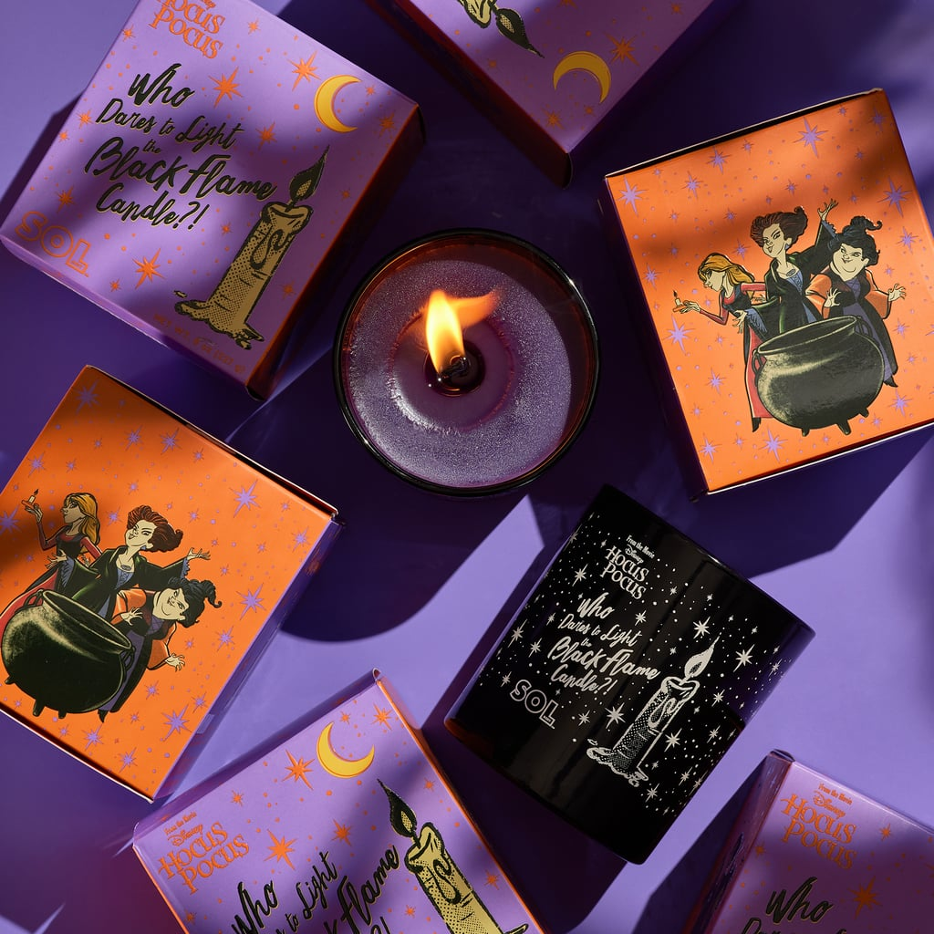 Purple and orange boxes featuring Sanderson Sisters behind a black cauldron. Top view of lit candle.