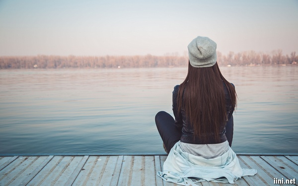 ảnh cô gái ngồi quay lưng về phía dòng nước