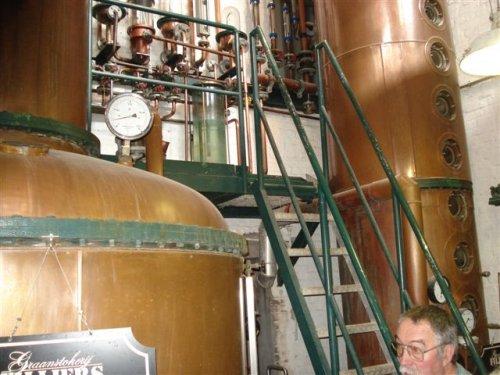 Rechts in beeld de distillatie toren om de alcohol van de wort te scheiden.