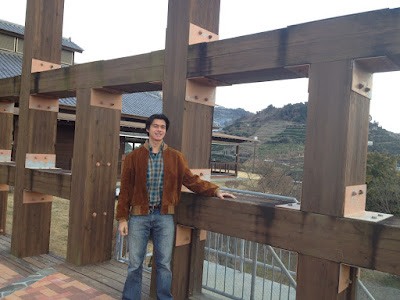 Brian standing by a wooden structure