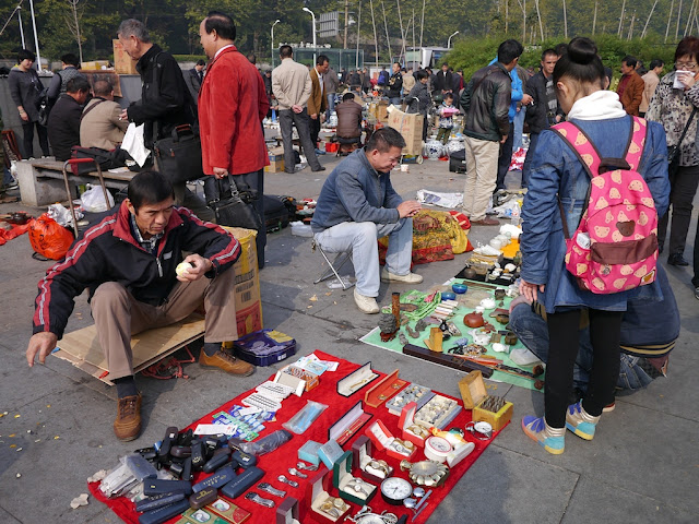 man peeling an egg at an outdoor antique market in Changsha, China