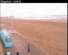 Completely empty Skegness promenade and wide wet sands except for lone figure of myself posing for webcam