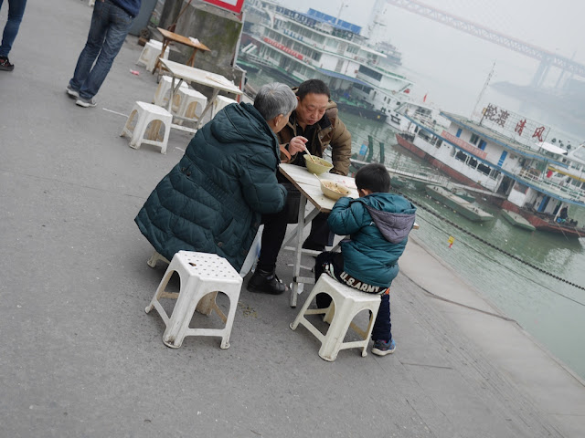 family eating noodles at an outdoor table