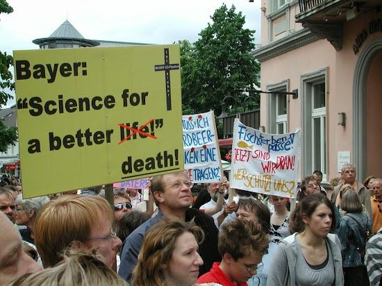 Transparent mit Totenkreuz beschriftet: »Bayer CO-Pipeline tosicher«. Und Plakatbeschriftung: »Bayer: ›Science for a better life‹«. Das Wort »life« durchgestrichen und durch »death« ersetzt.