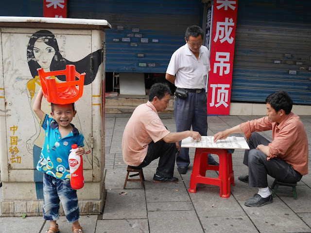boy smiling and holding a small plastic stool over his head near men playing xiangqi (Chinese chess)