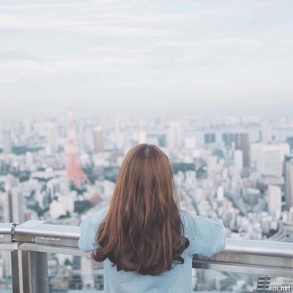ảnh cô gái buồn đứng nhìn xuống thành phố