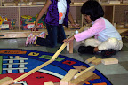 Children build ramps and explore motion in the block area.
