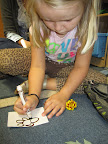 Child draws an object she found.