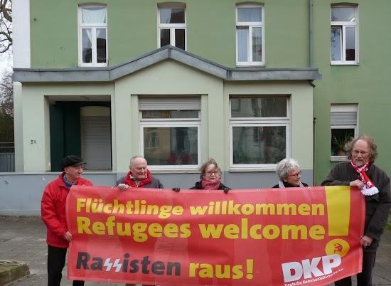 DKP-Mitglieder mit Transparent: »Flüchtlinge willkommen - Rassisten raus!«.