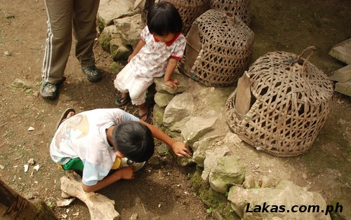 Children throwing spoonful amounts of water to the ground and carefully observing the ground
