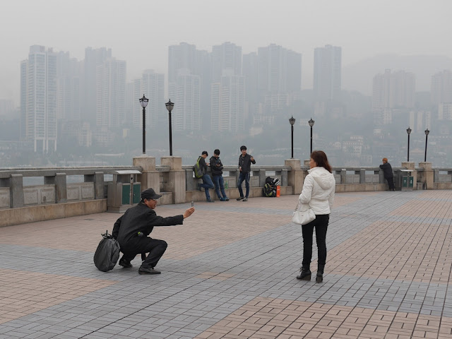 man photographing a woman with a mobile phone