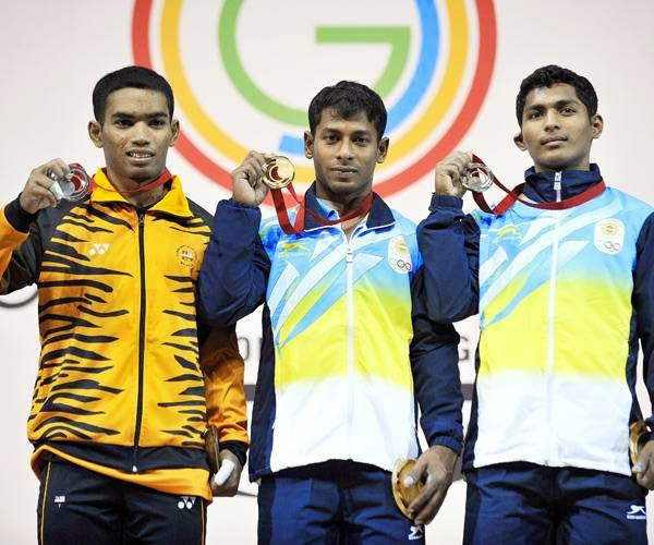 Malaysia's silver medalist Zulhelmi MD Pisol (L), India's gold medalist Sukhen Dey (C) and India's Ganesh Mali (R) celebrate with their medals on the podium at the medal ceremony for the men's weightlifting 56kg class at the SECC Precinct during the 2014 Commonwealth Games in Glasgow, Scotland on July 24, 2014.