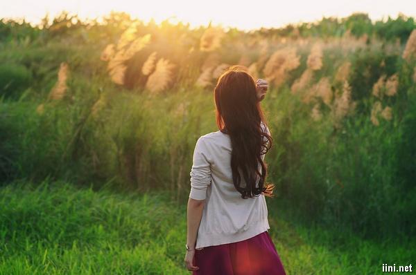 ảnh cô gái buồn quay lưng đi trên đồi cỏ