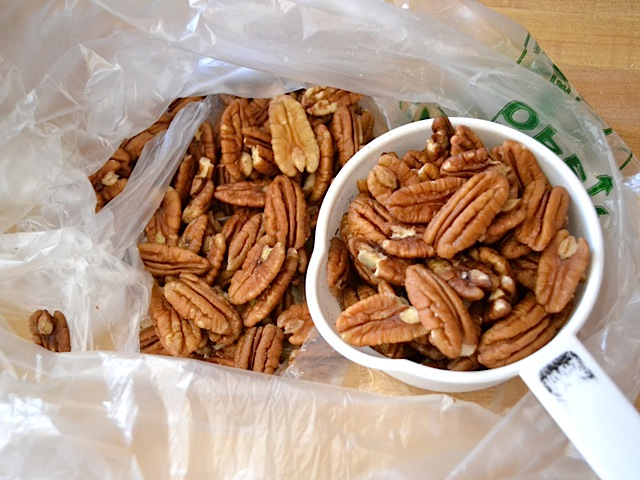 pecans in a bag being scooped out with measuring cup
