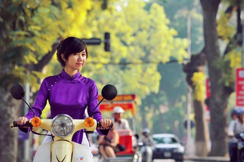 Cô gái mặc áo dài tím đi xe máy