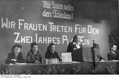 Frauen an Rednerpult und -tribüne, dahinter Wandschriften: »Wir Frauen wollen Frieden!« und »Wir Frauen treten für den Zwei Jahres Plan ein«.