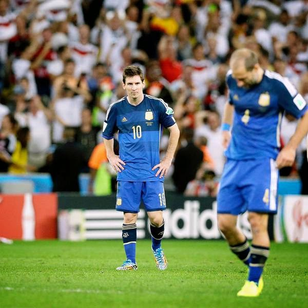 Argentina's Martin Demichelis, Lionel Messi and Pablo Zabaleta, from left, walk over the pitch after the World Cup final soccer match between Germany and Argentina at the Maracana Stadium, in Rio de Janeiro, on July 13, 2014.