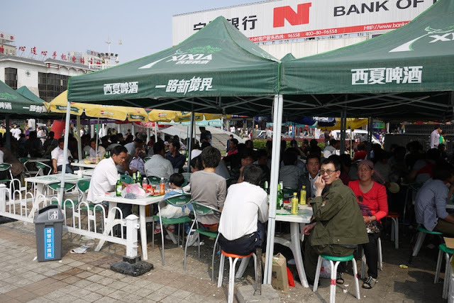 many people drinking under tents at Nanmen Square in Yinchuan, Ningxia, China