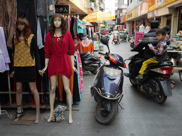 mannequins and man & young boy on a motorbike in Yangjiang, China